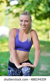 Happy young woman exercising on a grassy land
