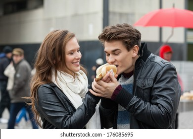 Happy young woman feeding hotdog to man outdoors
