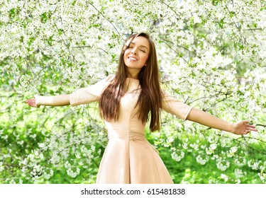 Happy young woman  in a flowering spring garden. Spring time. Flowers blossoms.