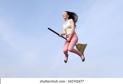 happy young woman flying with a broom