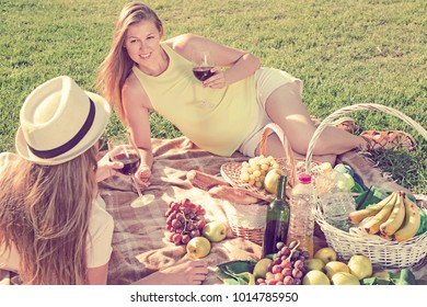 Happy young woman with friend sitting on green lawn drinking wine on picnic