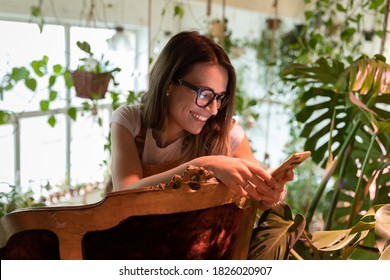 Happy young woman gardener in eyeglasses sitting on vintage chair in green house, holding smartphone, enjoying using mobile apps, chatting in social media, watching funny videos. Home gardening