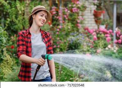 happy young woman gardener watering garden with hose. Hobby concept
