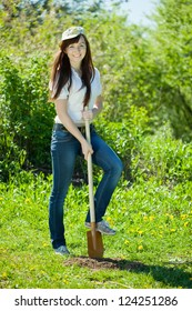 Happy young  woman gardening with spade in garden