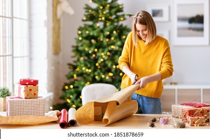 happy young woman gets ready for christmas and wrapping a gift