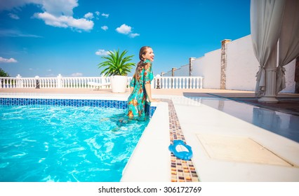 Happy young woman getting out of a  swimming pool. The woman is wearing a dress.