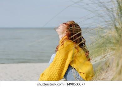 Joyeuse jeune femme qui se détend sur la plage de sable fin en automne en profitant de la chaleur du soleil