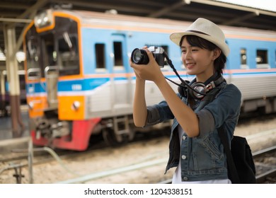 Happy young woman. girl with backpack taking photo of train station landscape view and smile happily. at the railway station, Backpacker concept, vintage train,blurred background