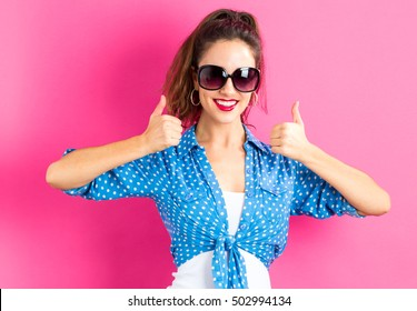 Happy young woman giving thumbs up on a pink background