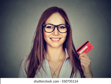 Happy young woman in glasses showing credit card