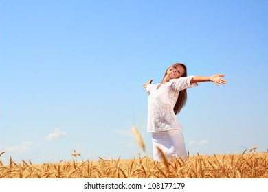 Happy young woman in golden wheat field