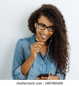 Happy young woman grinning as she listens to her favorite music with a beaming smile and look of absorbed anticipation