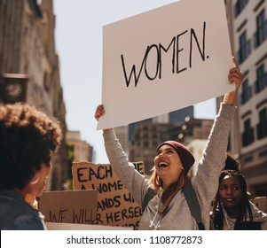 Happy young woman hand written protest sign at women's march. Group of females demonstrating outdoors.