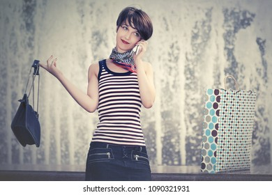Happy young woman with handbag calling on cell phone in city street Stylish fashion model with pixie hair wearing striped tank top and denim skirt