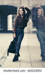 Happy young woman with handbag in city street. Stylish fashion model in leather fringe suede jacket and blue jeans