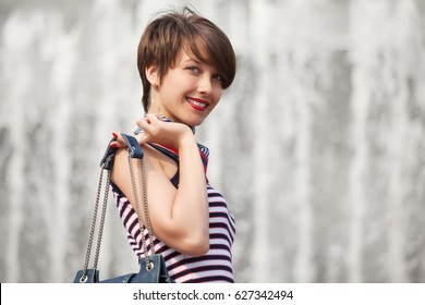 Happy young woman with handbag walking in city street. Stylish fashion model in tank top with pixie hair style outdoor