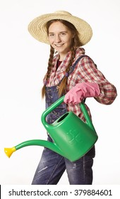 Happy young woman with hat, dungarees and watering can.