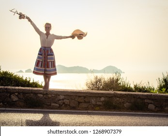 Happy young woman with hat in elegant colorful dress with skirt standing barefoot on a wall in front of the sea at sunset on Ponza Island Italy. Spread arms.