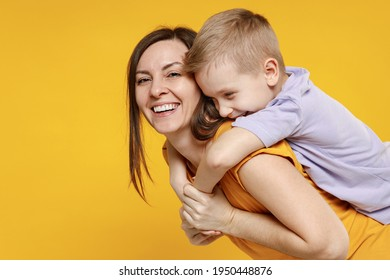 Happy young woman have fun with cute child baby boy 5-6-7 years old in violet t-shirt stand behind hug kiss. Mommy little kid son together isolated on yellow background studio Mother's Day love family
