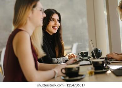 Happy young woman having casual talk during break in meeting. Multi-ethnic businesswomen having break during meeting.