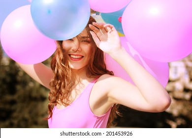 Happy young woman having fun with big colorful balloons