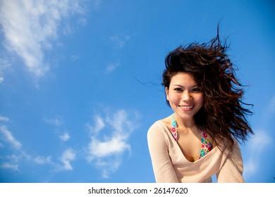 happy young woman having fun under blue sky