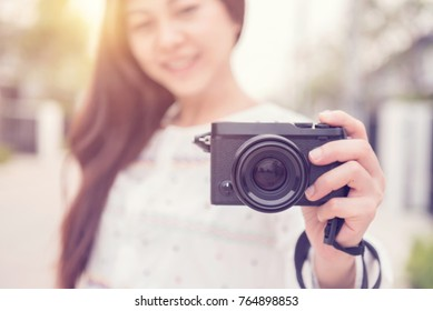 Happy young woman having fun with mirrorless camera travel photo of photographer Making pictures in hipster style