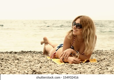 Happy young woman having good time at the seashore