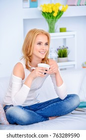 Happy young woman having a rest with a cup of tea and a magazine at home. Carefree weekend at home.
