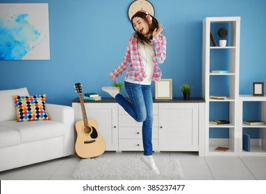 Happy young woman with headphones dancing and listening to music at home