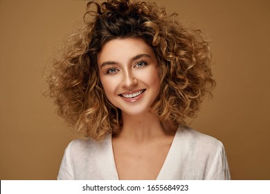 Happy young woman with healthy natural curls and delicate make-up posing at studio on brown studio background. Blonde woman with afro hairstyle smiling