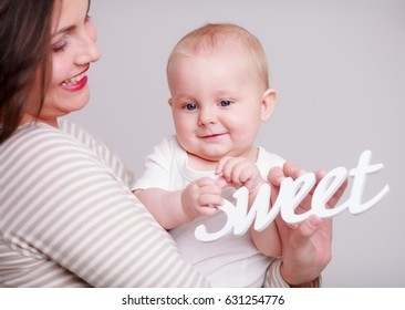 Happy young woman with her baby at home