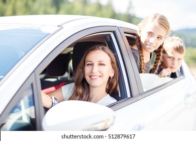 Happy young woman and her children sitting in a car and look out from windows. Family travel background image