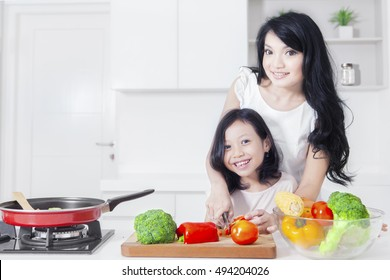 Happy young woman and her daughter smiling at the camera while cooking vegetable in the kitchen