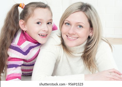 Happy young woman and her daughter lying on the floor and looking at camera