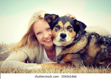 a happy young woman and her German Shepherd dog are laying on the grass outside hugging. Vintage style color.