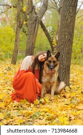 Happy young woman with her german shepherd dog in autumn park outdoor