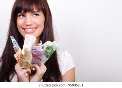 Happy young woman with her hands full of Euro bills
