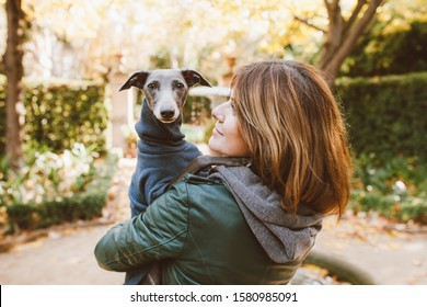 Happy young woman with her Italian Greyhound dog. Home pets. Young woman is holding and hugging her cute curious levrette puppy while walking in the park. Outdoor portrait