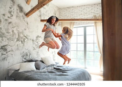 Happy young woman and her little cute daughter are having fun in bed while being at home together. Happy Mother's Day