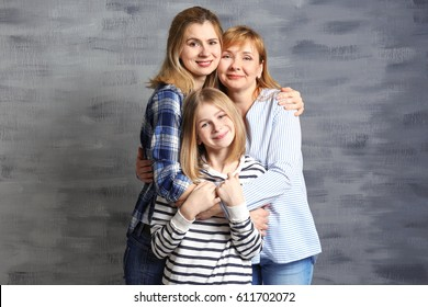 Happy young woman with her mother and daughter near color wall