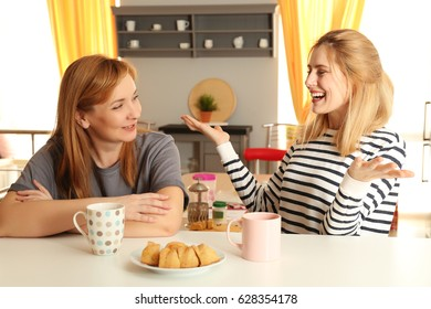 Happy young woman and her mother in kitchen