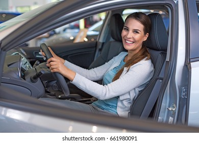 Happy young woman with her new car