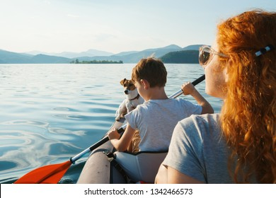 Happy young woman and her son with a dog Jack Russell Terrier are looking into the distance, rowing in an inflatable kayak on the water of mountain lake with a beautiful orange sunset. Family Weekend
