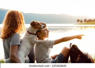 Happy young woman and her son with a dog Jack Russell Terrier are sitting on the bank of the lake in the grass and are watching the bright sunset. Family tourist backpack. Weekend with family. Camping