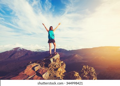 Happy Young Woman Hiker With Open Arms Raised at Sunset on Mountain Peak