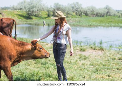Happy young woman hiker play with cows, country landscape