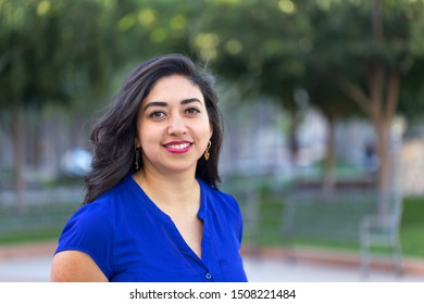 Happy young woman Hispanic college student outside
