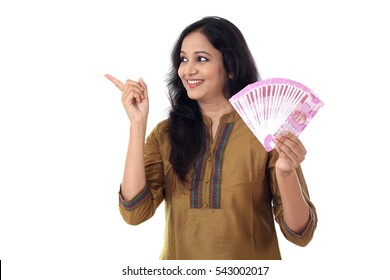 Happy young woman holding 2000 rupee notes against white