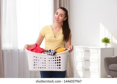 Happy young woman holding basket with laundry at home